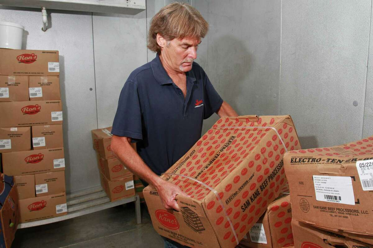 .(For the Chronicle/Gary Fountain June 24, 2014) Erik Mrok, owner/pitmaster at Lenox Bar-B-Q, stacking 70 pound cases of brisket in his cooler. A year ago each case was selling for about $154.00. With the increase in the price of beef, each case is now selling for about $225.00.