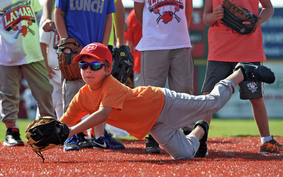 Ayden Goodman stretches for a grounder during the Lamar baseball camp at Vincent Beck Stadium on Wednesday. Photo taken Wednesday, June 18, 2014 Guiseppe Barranco/@spotnewsshooter Photo: Guiseppe Barranco, Photo Editor