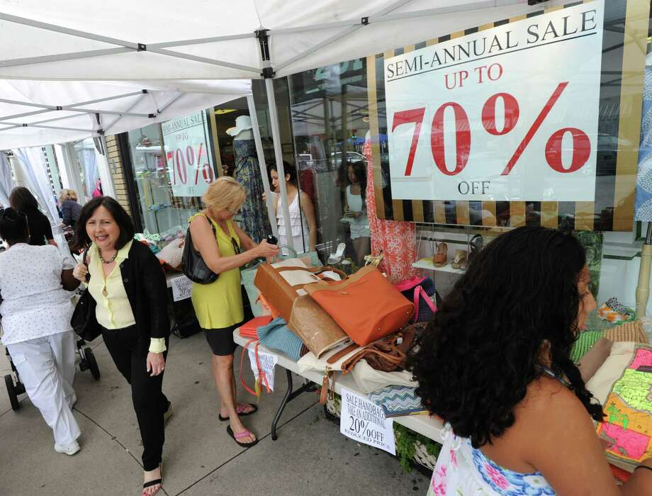 Shoppers in front of Shoes 'n' More during the annual Greenwich Sidewalk Sales in the central business district of Greenwich in 2013. The festivities will return from July 10 to 13, 2014. As in other years, merchants will be offering deep discounts and sales, but it takes a good strategy to pick up those treasures. Photo: Bob Luckey / Greenwich Time