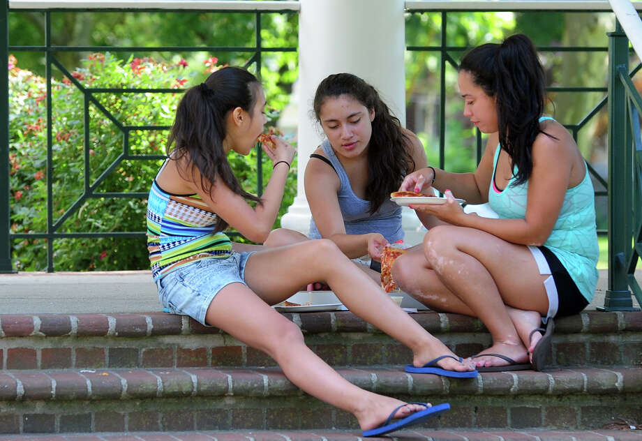 Julie Artiaga, 12, her sister Jaileen, 14, in back, and cousin Silvia Sincuir, 21, share a pizza at the gazebo on Paradise Green in Stratford, Conn. on Friday June 27, 2014. Photo: Christian Abraham / Connecticut Post