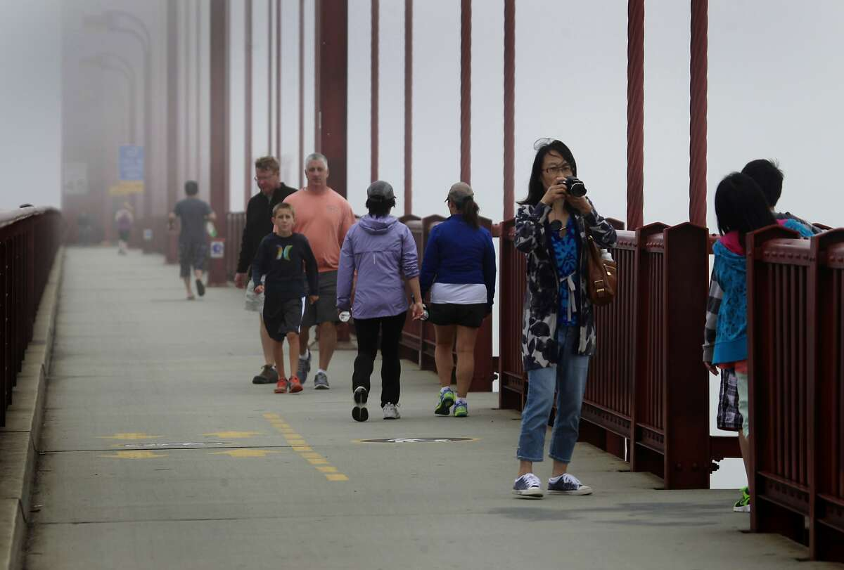 Sightseers stroll across the Golden Gate Bridge before the transit district board of directors vote unanimously in favor of erecting a suicide barrier on the iconic bridge in San Francisco, Calif. on Friday, June 27, 2014.
