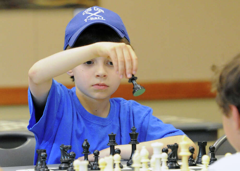 Benjamin Cooper, 9, of Cos Cob, makes a move in a chess match during a meeting of the Cos Cob Chess Club at the Cos Cob Library, Greenwich, Conn., Friday, June 27, 2014. Cooper is the club's president. Photo: Bob Luckey / Greenwich Time