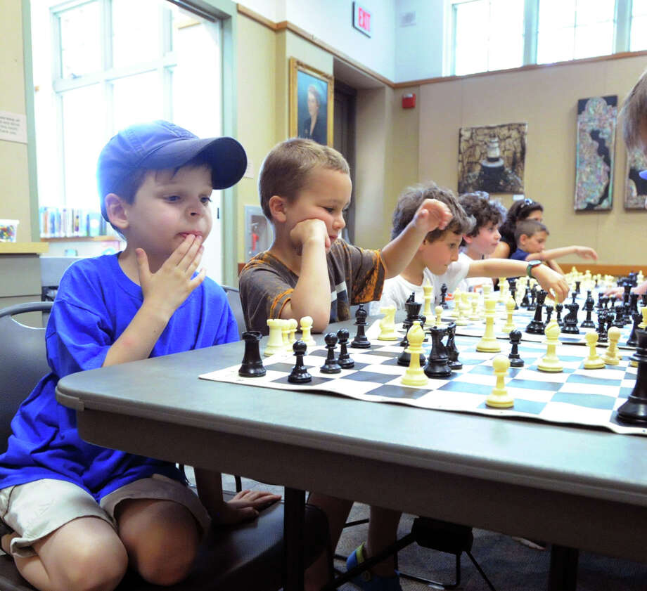 At left, Ethan Cooper, 7, of Cos Cob, contemplates his next move in a chess match during a meeting of the Cos Cob Chess Club at the Cos Cob Library, Greenwich, Conn., Friday, June 27, 2014. Photo: Bob Luckey / Greenwich Time
