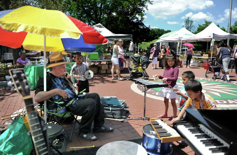 "Musician John Zanzal of New Fairfield, Conn. brings his ""Peace Soup"" program to the Danbury Farmer's Market, Friday, June 27, 2014. He encourages children to join him using his child-sized instruments that he provides. Photo: Carol Kaliff / The News-Times"