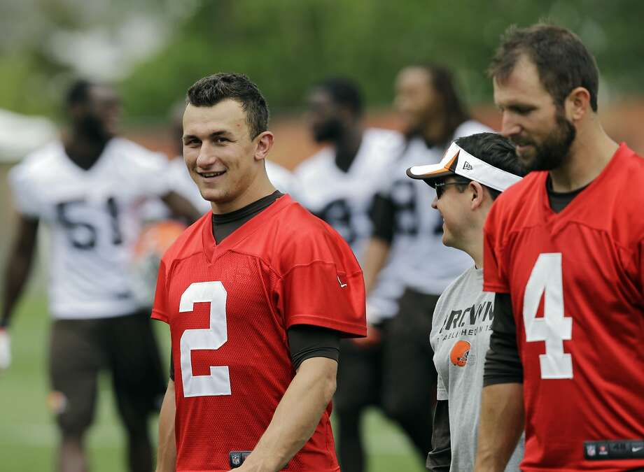 Cleveland Browns quarterback Johnny Manziel (2) walks off the field with Tyler Thigpen (4) and quarterbacks coach Dowell Loggains after a mandatory minicamp practice at the NFL football team's facility in Berea, Ohio Thursday, June 12, 2014.  (AP Photo/Mark Duncan) Photo: Mark Duncan, Associated Press