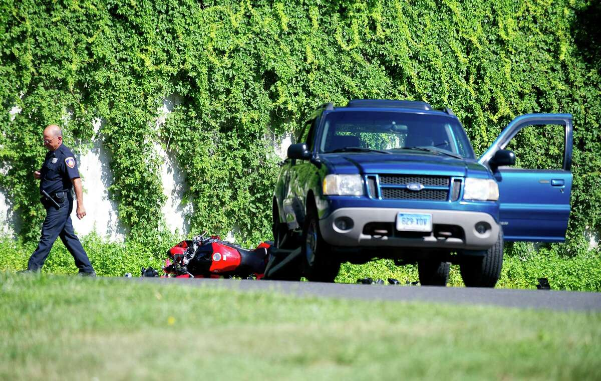 Stamford police officers work at the scene where a motorcycle and Ford Explorer collided at the intersection of Harvard Ave. and Commerce Road in Stamford, Conn., on Friday, June 27, 2014.