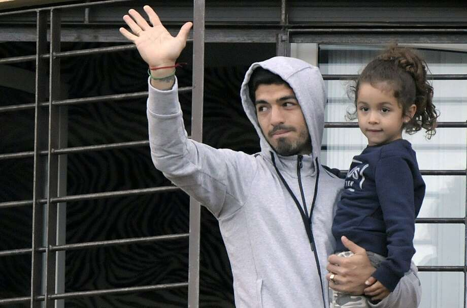 Uruguay soccer player Luis Suarez holds his daughter as he greets fans from his home's balcony on the outskirts of Montevideo. Photo: Matilde Campodonico, Associated Press