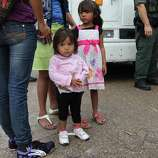 "JUNE 25, 2014, 5:04 PM, GRANJENO, TEXAS – Immigrants children wait with parents as Border Patrol agents process them in Granjeno, Texas. The city is just north of  ""El Rincon del Diablo,"" the Devil's Corner, a hotbed of illegal border crossing on the Rio Grande by juvenile and mothers with children immigrants from Central America."