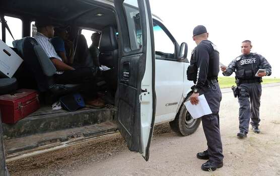 JUNE 27, 2014, 8:49 AM, HIDALGO COUNTY, TEXAS - Hidalgo County Sheriff's Department Tactical Team Senior Deputy Sheriff Tony Castellano, left, and Senior Deputy Rene Rivera check out a van near the intersection of FM 490 and U.S. 281. The van was traveling on a known human trafficking road and the driver was given a warning after running a stop sign. The men in the van had Mexican passports and Visas. They were on their way to pick watermelons. Photo: Jerry Lara, San Antonio Express-News / ©2014 San Antonio Express-News