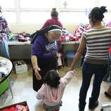 June 26, 2014, 4:46 p.m., Brownsville - Sister Evelyn Morales of Incarnate Word Academy in Brownsville reaches out to help a mother and her child at a welcoming center at Immaculate Conception Church. The center was opened to provide aid in the form of clothing, food and respite to the recent influx of immigrants crossing over the border.