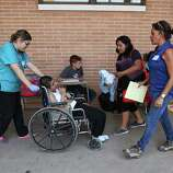 June 26, 2014, 5:18 p.m., Brownsville, Texas - Volunteers from Catholic Charities aid a young boy in a mud-caked wheelchair and his mother at the immigrant welcoming center at Immaculate Conception Church. Groups of unauthorized immigrants were released by Homeland Security at the bus station near the church and were escorted by Catholic Charities volunteers to the center to receive aid in the form of clothing, food and respite.