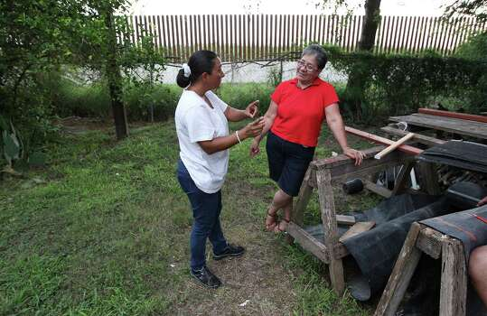 June 26, 2014, 8:18 p.m., Brownsville, Texas - Brownsville residents Elizabeth Garcia (left) and Elisa Cortez chat in Cortez's backyard which was shortened due to the placement of a border fence. Cortez lives about a mile from the Rio Grande River which borders Mexico. Photo: Kin Man Hui, San Antonio Express-News / ©2014 San Antonio Express-News