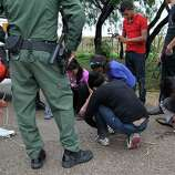 "JUNE 25, 2014, 5:02 PM, GRANJENO, TEXAS - Immigrants remove shoelaces as U.S. Border Patrol agents processed them in Granjeno, Texas. The city is just north of  ""El Rincon del Diablo,"" the Devil's Corner, a hotbed of illegal border crossing on the Rio Grande by juvenile and mothers with children immigrants from Central America. Agents confiscate the immigrants' shoelaces to keep them from harming themselves."