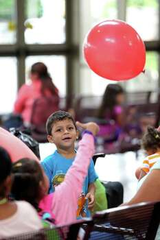 JUNE 26, 2014, 3:34 PM, MCALLEN, TEXAS - After an arduous two-week journey from San Salvador, El Salvador, five-year-old Oswaldo Ramirez, 5, is fascinated by a balloon while waiting with family at the bus station. Ramirez was traveling with his mother and two siblings as they headed to Maryland after being processed by U.S. Immigrations. Photo: Jerry Lara, San Antonio Express-News / ©2014 San Antonio Express-News