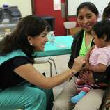 JUNE 26, 2014, 2:29 PM, MCALLEN, TEXAS - Catholic Charities volunteer Carmen Garza, left, plays with one-year-old Belinda Gomez, held by her mother, Maria Julia, 20, at the Sacred Heart shelter. The Guatemalans were headed to Atlanta.
