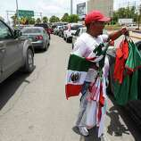 June 26, 2014, 1:41 p.m., Matamoros, Tamaulipas, Mexico - Vendor Andy (no last name given) offers to sell Mexico soccer jerseys and Mexican flags to drivers waiting in their vehicles as they cross the international bridge to Brownsville.