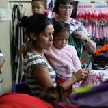 June 26, 2014, 4:39 p.m., Brownsville, Texas - Martina Santos Barrera Garcia (center) with her daughter, Lisbeth, pick out clothing at an immigrant welcoming center at Immaculate Conception Church run by Catholic Charities after she was released by Homeland Security. Garcia was released with a group of unauthorized immigrants at the bus station near the church and was walked over by Catholic Charities volunteers to the center to receive aid in the form of clothing, food and respite. According to paperwork for Garcia she was from the Republic of Honduras.