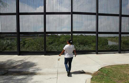 June 26, 2014, 11:45 a.m., Brownsville, Texas - Brownsville resident Elizabeth Garcia walks toward a border fence along the Rio Grande River to check on traffic at the Brownsville Gateway bordering crossing before going over to Matamoros, Mexico. Garcia makes frequent trips to the Mexico city across of Brownsville to shop and see family. Photo: Kin Man Hui, San Antonio Express-News / ©2014 San Antonio Express-News