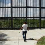 June 26, 2014, 11:45 a.m., Brownsville, Texas - Brownsville resident Elizabeth Garcia walks toward a border fence along the Rio Grande River to check on traffic at the Brownsville Gateway bordering crossing before going over to Matamoros, Mexico. Garcia makes frequent trips to the Mexico city across of Brownsville to shop and see family.