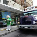 June 26, 2014, 12:01 p.m., Matamoros, Tamaulipas, Mexico - An individual dressed as a caricature for Farmacias Similares, a pharmacy, attempts to entice customers to shop at their store.