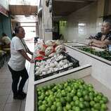 June 26, 2014, 12:14 p.m., Matamoros, Tamaulipas, Mexico - Brownsville resident Elizabeth Garcia (left) chats with shopkeeper Lourdes Sanchez at a market in Matamoros. Garcia often crosses the border into Mexico to shop and visit family.