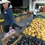 June 26, 2014, 12:17 p.m., Matamoros, Tamaulipas, Mexico - A man walks by stands of fruit in Matamoros.