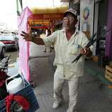 June 26, 2014, 12:30 p.m., Matamoros, Tamaulipas, Mexico - Alejandro Picasso attempts to sell windshield wipers near a market in Matamoros. Picasso claimed he need to sell the wipers to support his beer and marijuana habit. He rides his bicycle approximately 25 kilometers each day into town to work.