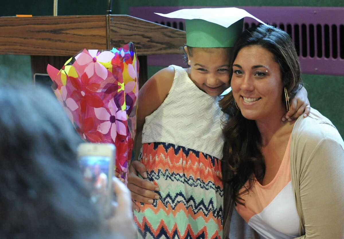 Kindergarten graduate Izabella Been, 5, of Cohoes gets her photo taken with her mother, Julia Lawson, after the annual Moving Up Ceremony at the Ark Community Charter School Friday, June 27, 2014 in Troy, N.Y. The charter school has been targeted for closure. (Lori Van Buren / Times Union)