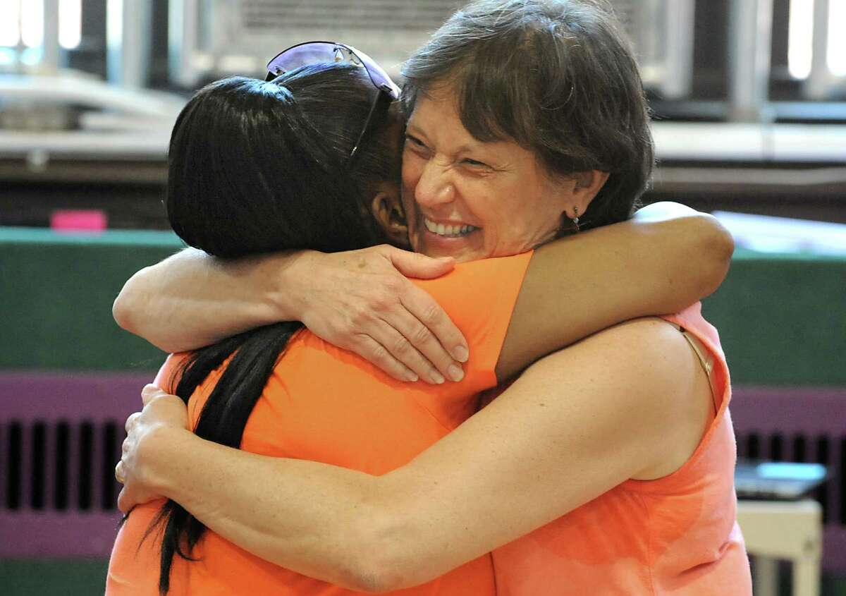 Parent Cindy Brown, left, gives Ark Community Charter School administrator Petra Hahm a big hug at the end of the annual Moving Up Ceremony School Friday, June 27, 2014, at the Ark Community Charter School in Troy, N.Y. The charter school has been targeted for closure. (Lori Van Buren / Times Union)