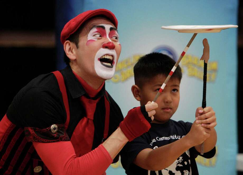 Ringling Bros. and Barnum & Bailey Clown Rob Lok shows Christopher Gee how to spin a plate during his performance at the Chinese Community Center on Friday, June 27, 2014, in Houston, Tx. Photo: Mayra Beltran, Houston Chronicle / © 2014 Houston Chronicle