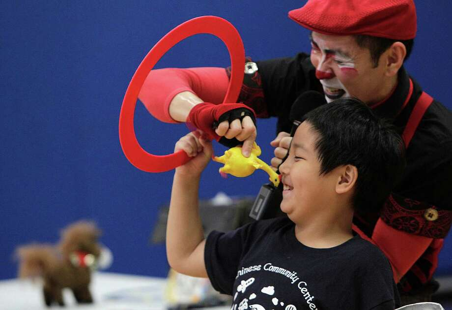 "William Frederick laughs while helping Ringling Bros. and Barnum & Bailey Clown Rob Lok with an ""animal stunt"", a rubber chicken, during his performance at the Chinese Community Center on Friday, June 27, 2014, in Houston, Tx. Photo: Mayra Beltran, Houston Chronicle / © 2014 Houston Chronicle"