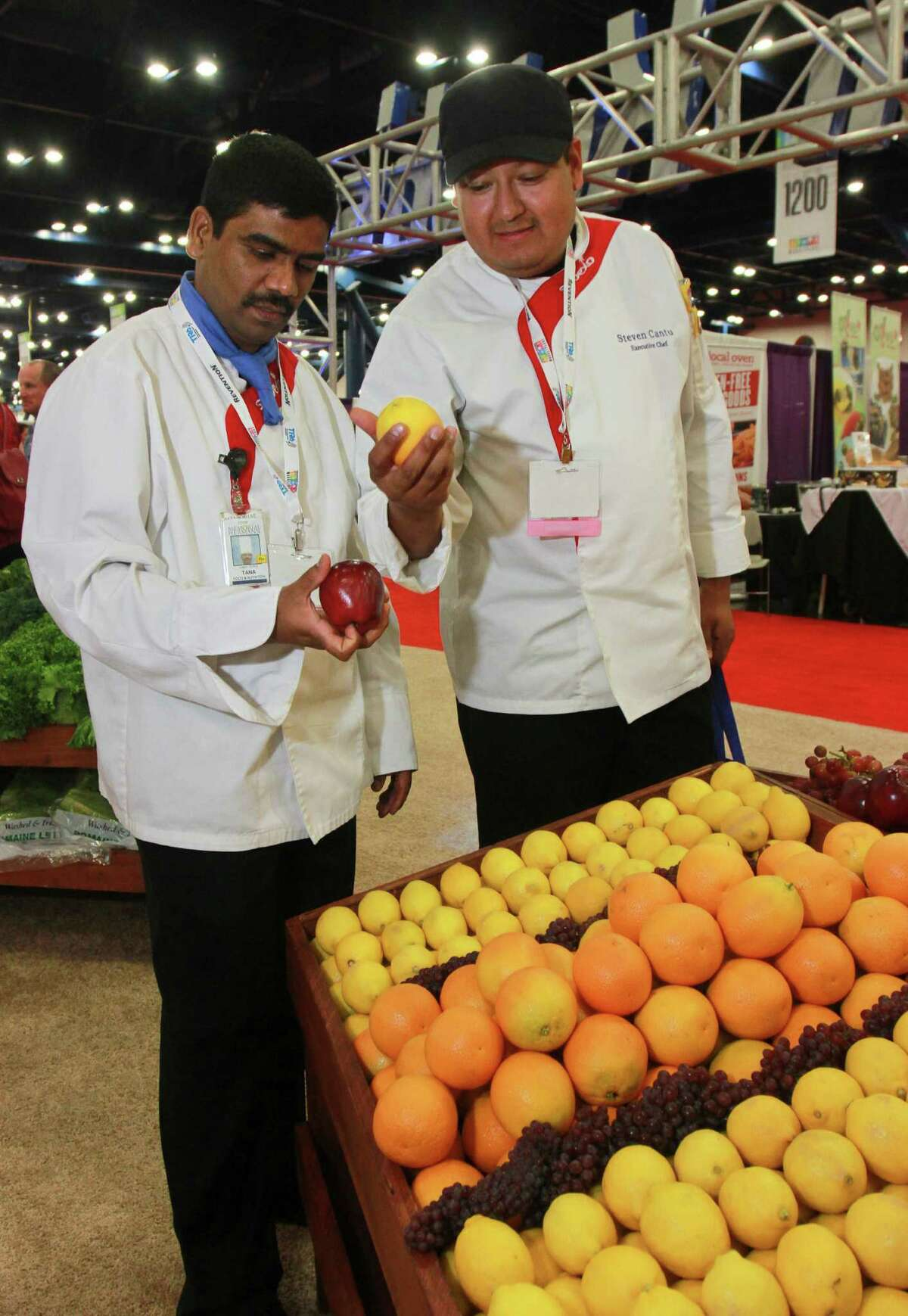 Tana Jothi (left), a Memorial Hermann sous chef, and Steven Cantu, executive chef with Memorial Hermann Southeast Hospital, look at the produce at Ben E. Keith Co. food service distributors at the 76th annual Texas Restaurant Association foodservice show held recently at the George R. Brown Convention Center in Houston.