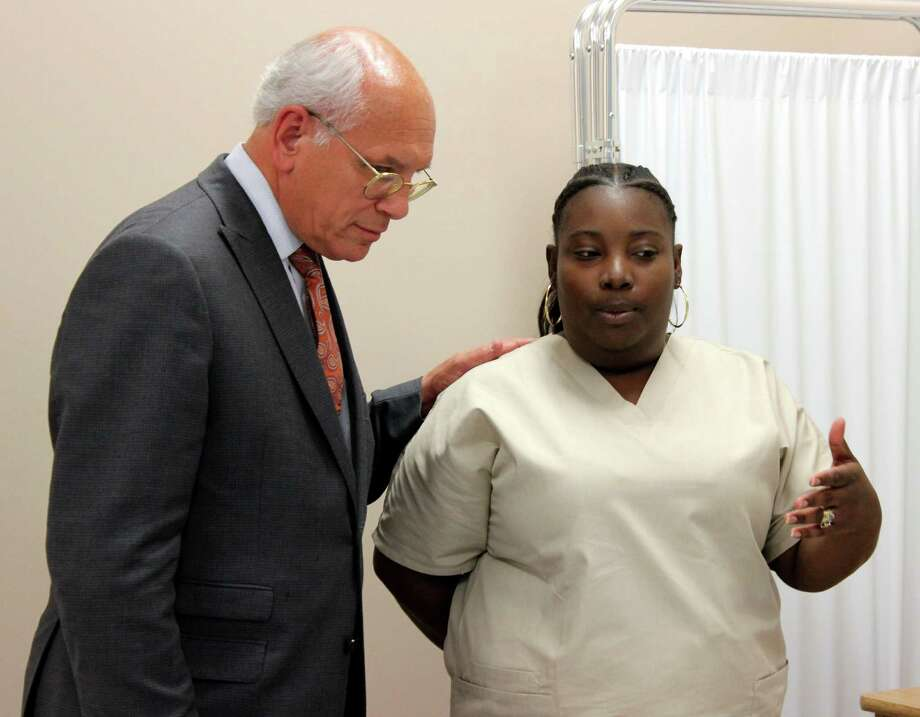 Congressman Paul Tonko, left, and Olivia Cook, right, talk following a healthcare skills demonstration held during an open house at the Schenectady County Community College City Center Friday afternoon, June 27, 2014, in Schenectady N.Y. The open house was held to celebrate the Health Profession Opportunity Grant Program. The program provides preparation and support to low-income individuals to gain employment in high demand healthcare jobs. (Selby Smith / Special to the Times Union) Photo: Selby Smith / 00027489A