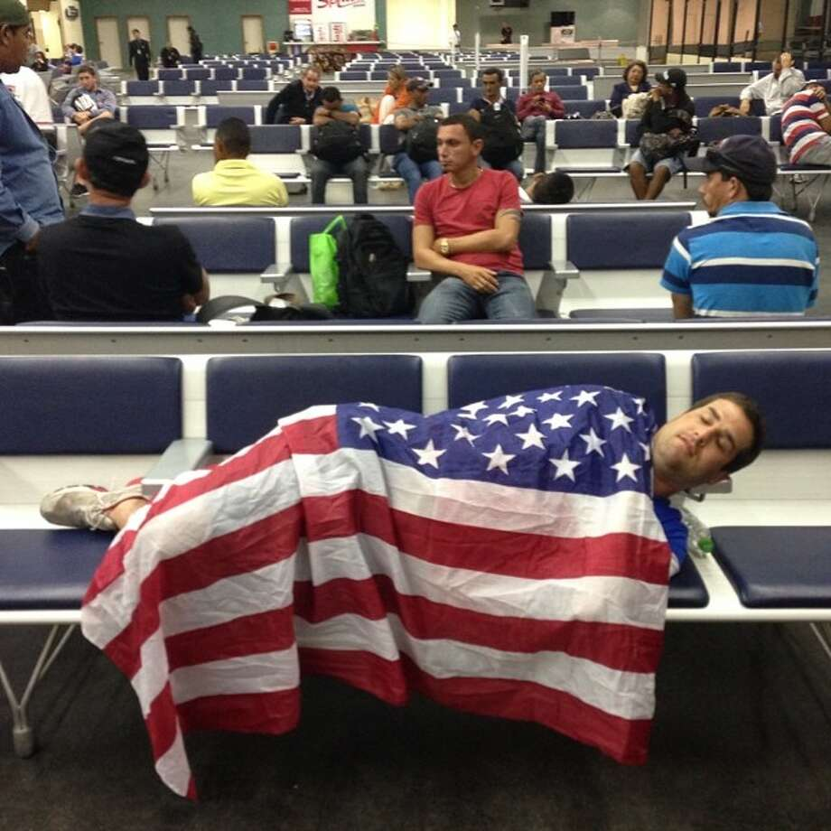 Derek Stephenson of Washington naps at Manaus airport the morning after he watched USA and Portugal tie 2-2.  Photo: Julio Cortez, Associated Press / AP