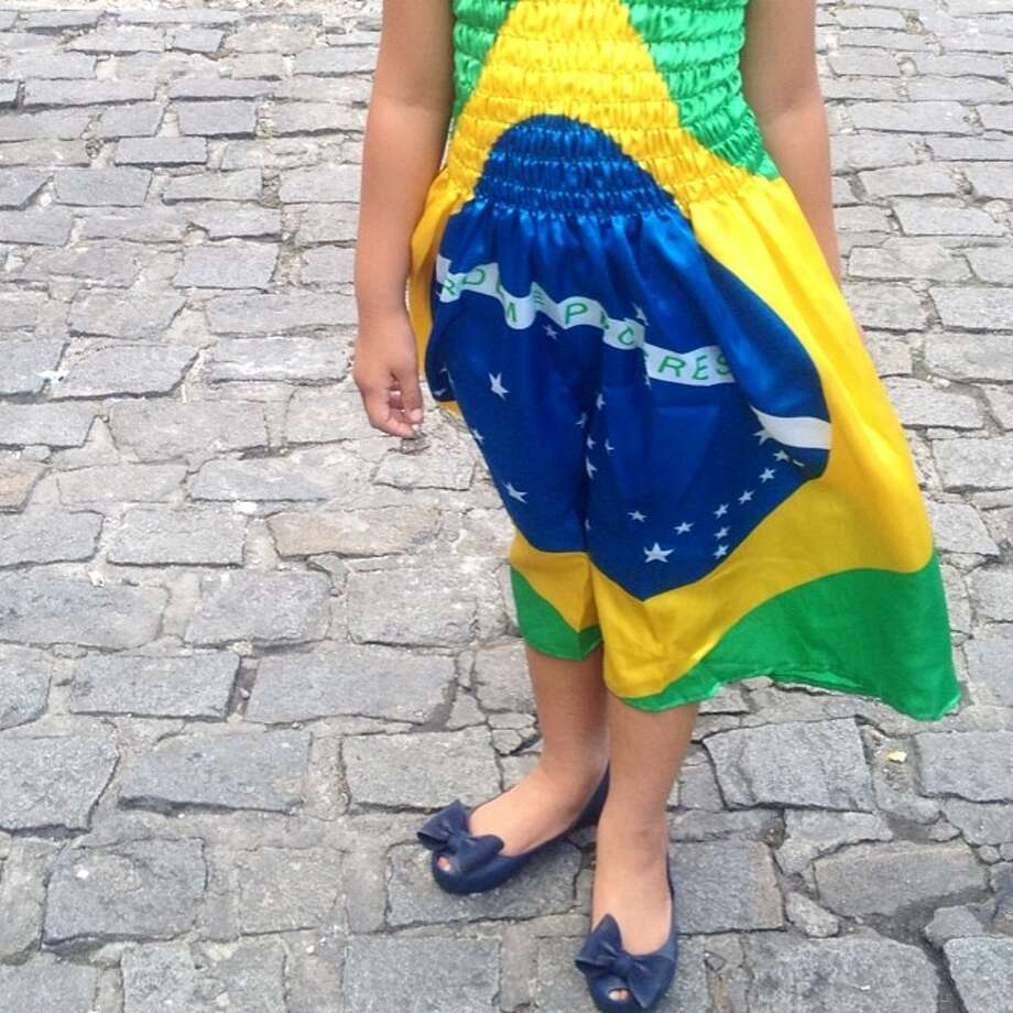A girl in a dress with the Brazil flag in Salvador, Brazil.  Photo: Natacha Pisarenko  A Couple In S, Associated Press / AP