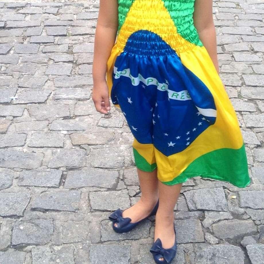 A girl in a dress with the Brazil flag in Salvador, Brazil. Photo: Natacha Pisarenko  A Couple In S, Associated Press / AP