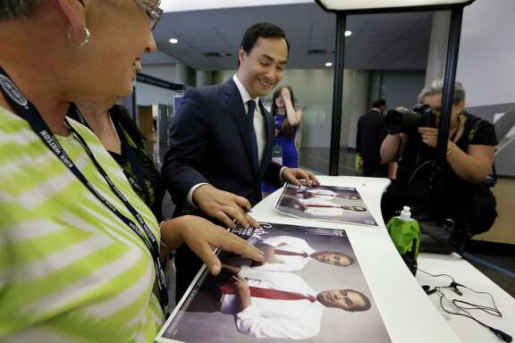 U.S. Rep. Joaquin Castro, D-Texas, doesn't seem to mind autographing photos of himself with his twin brother, Julian, on Friday during the Texas Democratic Convention at the Dallas Convention Center.