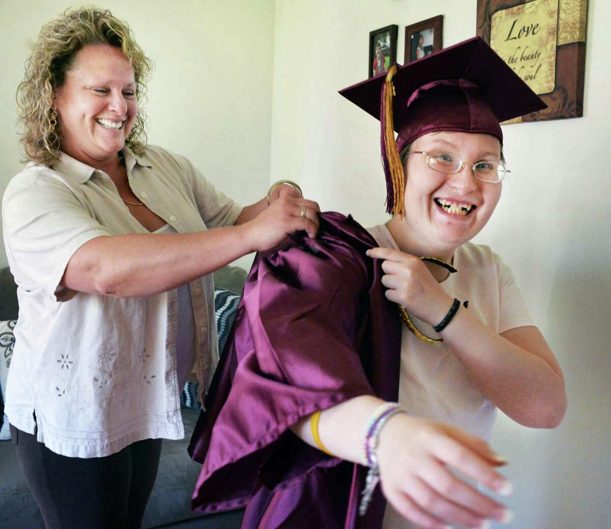 Denise Famiano, left, helps her daughter Brittany Manning, 21, try on her cap and gown as they prepare for the Colonie Central School graduation ceremony Friday, June 27, 2014, at the group home where Manning lives in Colonie, N.Y. Manning is developmentally disabled and suffers from Prader-Willi syndrome, a rare genetic disease whose chief symptom is uncontrollable hunger that is impossible to satisfy and can lead to life-threatening obesity and other complications. She graduated from Colonie Central School on Friday. (John Carl D'Annibale / Times Union)