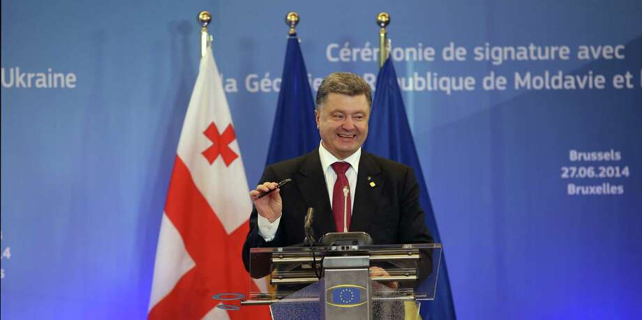 "Ukrainian President Petro Poroshenko holds up a pen after a signing ceremony at an EU summit in Brussels on Friday, June 27, 2014. The Ukrainian President Petro Poroshenko has signed up to a trade and economic pact with the European Union, saying it may be the ""most important day"" for his country since it became independent from the Soviet Union. The European Union signed similar association agreements with two other former Soviet republics, Moldova and Georgia. (AP Photo/Olivier Hoslet, Pool) ORG XMIT: VLM125 Photo: Olivier Hoslet / EPA Pool"