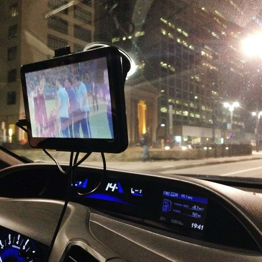 Traveling 14 kph while watching World Cup soccer in a cab in downtown Sao Paulo. Photo: Julio Cortez, Associated Press / AP
