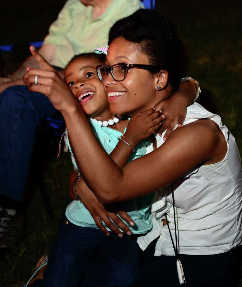 Tracy-Ann Samuel, of Bridgeport, and her daughter Kristin, 3, watch the fireworks during the Barnum Festival's Skyblast Fireworks and Greater Bridgeport Symphony Pops Concert at Seaside Park in Bridgeport, Conn. on Friday June 27, 2014. Photo: Christian Abraham / Connecticut Post
