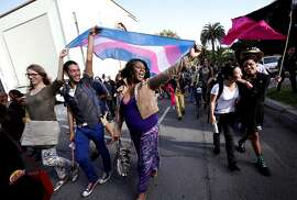 Ms. Jajah Desmon, center, of San Francisco, and Anthony Escobar, left, and Audrey Vogel, far left, both of Berkeley, carry a flag during Trans March 2014 in San Francisco, Calif., on Friday, June 27, 2014.