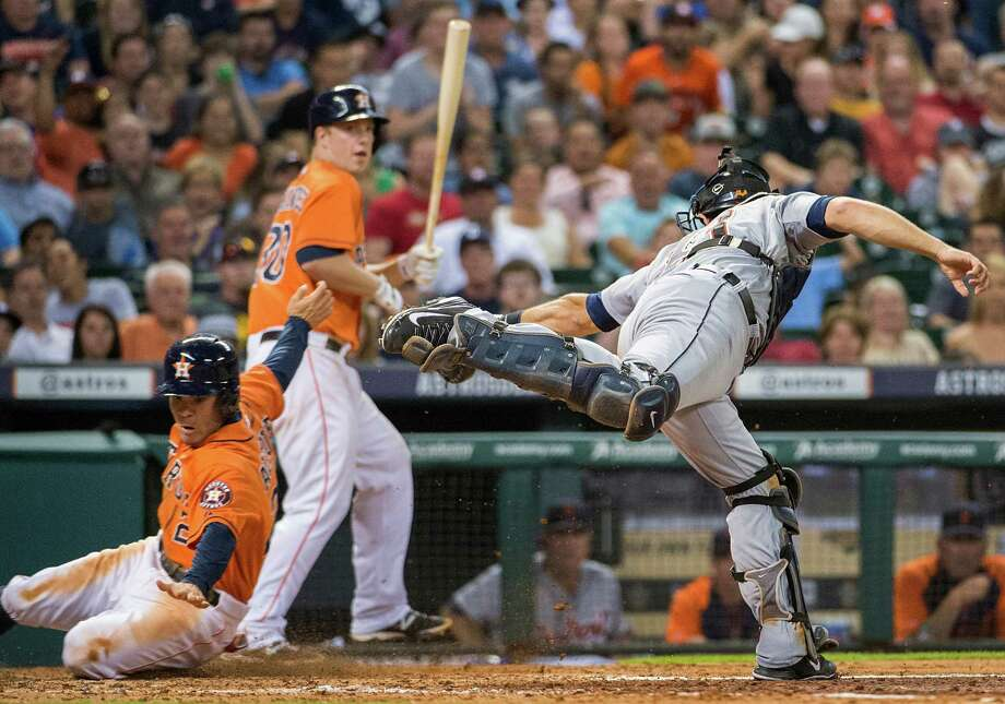 Astros second baseman Jose Altuve gets past the tag from Tigers catcher Alex Avila as he steals home with Matt Dominguez batting in the fifth inning Friday night. Photo: Smiley N. Pool / © 2014  Smiley N. Pool