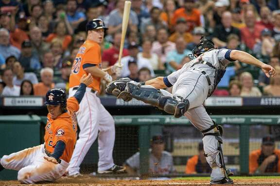 Astros second baseman Jose Altuve gets past the tag from Tigers catcher Alex Avila as he steals home with Matt Dominguez batting in the fifth inning Friday night.