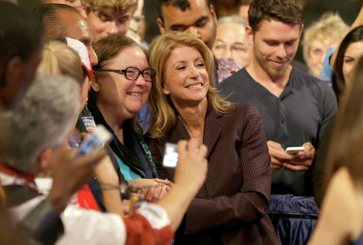 Gubernatorial hopeful and state Sen. Wendy Davis, center, poses for photos with supporters after speaking at the Dallas Convention Center during the Texas Democratic Convention in Dallas, Friday, June 27, 2014. Davis became a Democratic sensation nationally with a 12-plus hour Texas Senate filibuster last summer that temporarily delayed passage of strict abortion restrictions statewide. (AP Photo/LM Otero)