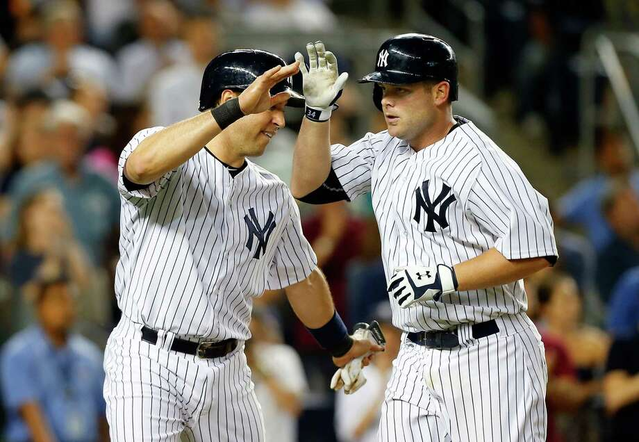 NEW YORK, NY - JUNE 27:  Brian McCann #34 of the New York Yankees (R) celebrates his eighth inning two run home run against the Boston Red Sox with teammate Mark Teixeira #25 at Yankee Stadium on June 27, 2014 in the Bronx borough of New York City.  (Photo by Jim McIsaac/Getty Images) ORG XMIT: 477585681 Photo: Jim McIsaac / 2014 Getty Images
