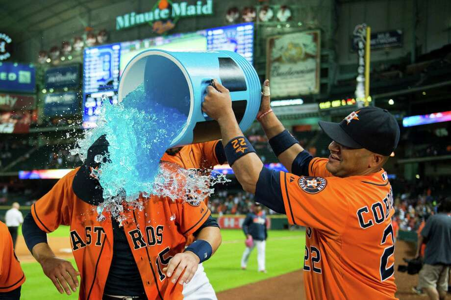 Jason Castro is doused by fellow catcher Carlos Corporan after hitting a walkoff home run in the 11th to give the Astros a 4-3 win over the Tigers. Photo: Smiley N. Pool / © 2014  Smiley N. Pool