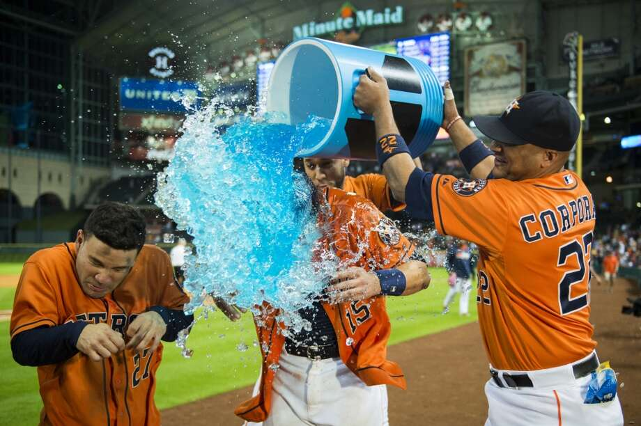 June 27: Astros 4, Tigers 3  Jason Castro and Jose Altuve are doused by catcher Carlos Corporan after Castro hit a walk off home run in the 11th inning. Photo: Smiley N. Pool, Houston Chronicle