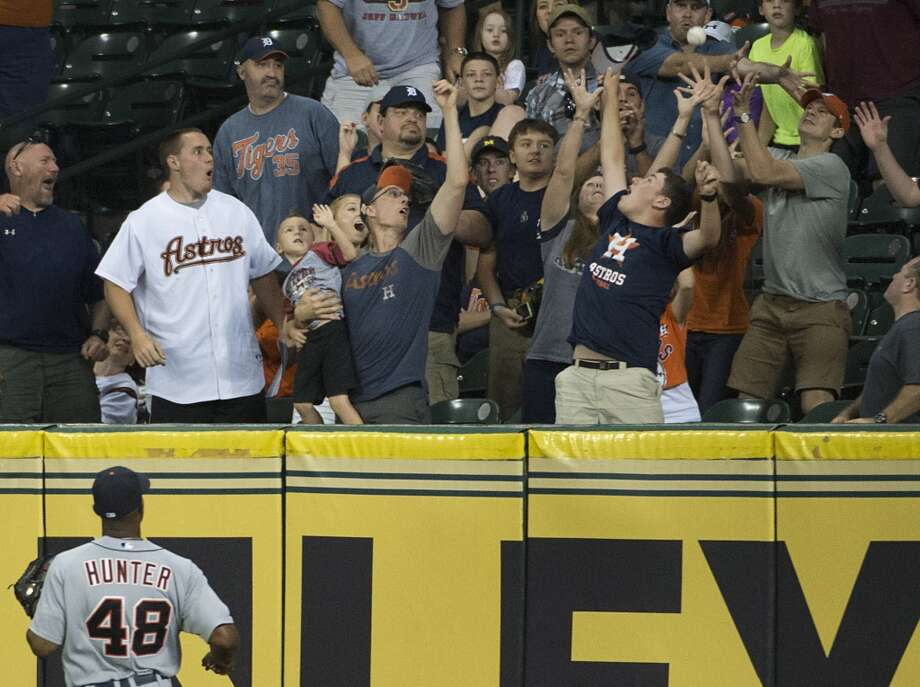 Tigers right fielder Torii Hunter can only watch as fans reach for the ball on a game-winning home run by Jason Castro during the 11th inning. Photo: Smiley N. Pool, Houston Chronicle