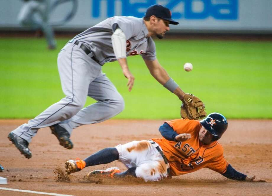 Jose Altuve is safe at third base as the throw gets past  Tigers third baseman Nick Castellanos during the first inning. Photo: Smiley N. Pool, Houston Chronicle
